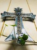 Blaues Kreuz mit grünem Efeu lizenzfreie stockbilder