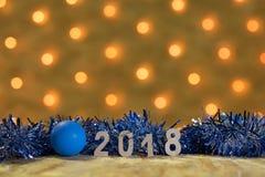 Blaues Lametta und ein Ball mit Zahlen von 2018 auf einer Tabelle auf dem Hintergrund einer neues Jahr ` s Girlande mit goldenen  Stockfotografie