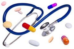 Blaues medizinisches Stethoskop mit Pillen und Tabletten Lizenzfreie Stockfotos