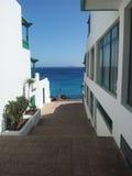Blaues Meer durch eine Straße Lizenzfreie Stockbilder