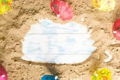 Blaues Meer, Himmel u Sand auf einem hölzernen Brett mit Strandschirmen lizenzfreies stockbild