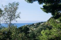 Blaues Meer, klarer Himmel, Bäume, Häuser Stockfotografie