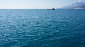 Blaues Meer mit Berg und Schiffen auf Horizont Stockfoto