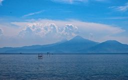 Blaues Meer mit Hintergrund des blauen Himmels und der Berge Stockfotografie