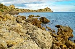Blaues Meer, schöner Himmel, große Steine auf einem felsigen Ufer auf dem Schwarzen Meer fahren, Krim, Novy Svet die Küste entlan Lizenzfreie Stockbilder