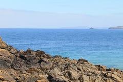 Blaues Meer und felsige Küsten- und entfernteländer bei Cornwall, England Stockfoto