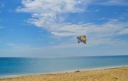 Blaues Meer und sandiger Strand an einem sonnigen Tag und Drachen im Himmel stockbild