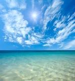 Blaues Meer und Sonne im Himmel Stockbild