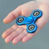 Blaues Metallnehmen populäres Unruhe-Spinnerspielzeug auf der Palme Ihrer Hand, sie Stockbild