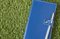 Blaues Notizbuch gesetzt auf Gras Lizenzfreie Stockfotografie