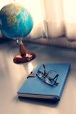 Gläser auf Notizbuch mit Kugel lizenzfreie stockfotografie