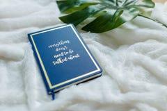 Blaues Notizbuch stellte nicht weißen weichen Stoff mit grünen künstlichen Blättern ein Stockbild