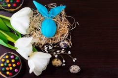 Blaues Osterei in Form von Kaninchen im Nest mit Weidenniederlassungen, weißen Tulpen, kleinen Kuchen und Wachteleiern Lizenzfreie Stockfotos