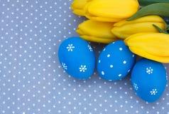 Blaues Osterei mit gelben Tulpen Lizenzfreies Stockbild
