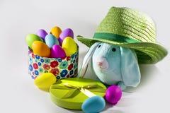 Blaues Ostern-Häschen mit grünem Strohhut und Geschenkbox mit bunten Eiern Ostern Lizenzfreie Stockfotografie