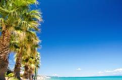Blaues Paradieswasser von Toroneos-kolpos Golf, blauer Himmel, weiße Wolken und Palmen auf dem Strand von Pefkohori, Halkidiki Ka lizenzfreie stockfotos