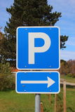 Blaues parkinglot Zeichen mit rechtem Pfeil und Himmel im Hintergrund Lizenzfreie Stockbilder