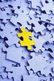 Blaues Puzzlespiel mit einem gelben Element stockbilder