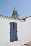 Blaues Retro- Fenster und Kirche mit Uhr Stockfoto