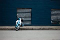 Blaues Rollerfahrrad gegen eine blaue Wand stockfoto