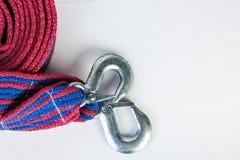 Blaues/rotes Zugseil mit Metallhaken auf einem weißen backgr Stockfotos