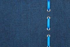 Blaues Satinband wird in ein dunkles Denimgewebe eingefügt Ansicht von oben Stockfotografie