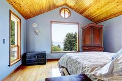 Blaues Schlafzimmer mit hölzernem Decken- und Bettinnenraum. Stockfotos