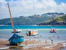 Blaues Segelboot auf dem Strand während der Ebbe Stockbild