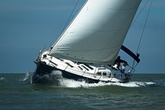 Blaues Segelboot, das Geschwindigkeit unter blauem Himmel nimmt Lizenzfreie Stockfotografie