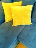 Blaues Sofa mit hellen gelben Kissen Stockfotografie