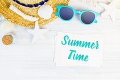 Blaues Sommerzeitwort auf weißer Karte am hölzernen Tisch mit sunglasse Stockfotos
