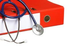 Blaues Stethoskop und rote Mappe lokalisiert auf Weiß Lizenzfreie Stockfotos