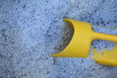 Blaues Streusalz mit einer gelben Schaufel Stockfoto