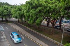 Blaues Taxi Parkplatz an Taxiendwartepassagier unter grünen Bäumen lizenzfreie stockfotos