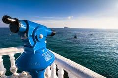 Blaues Teleskop, das heraus zur Insel von Benidorm schaut Stockfotografie