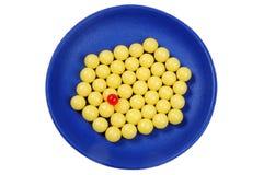 Blaues Tellervoll Gelb lässt Vitamin und rote Pille fallen Lizenzfreie Stockfotos