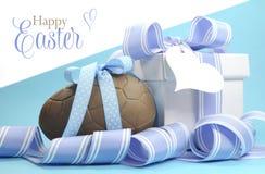 Blaues Thema glückliches Ostern-Schokoladenei und -Geschenkbox mit Streifenband Stockfotos