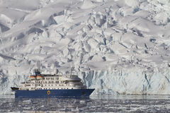Blaues touristisches Schiff auf dem Hintergrund von Sommertagesgletschern Lizenzfreies Stockfoto