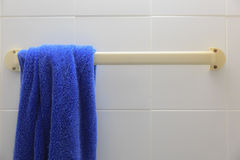 Blaues Tuch, das an einem Aufhänger im Badezimmer hängt Stockbild