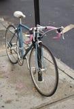 Blaues und rosa Fahrrad auf dem Bürgersteig Stockfotos