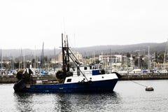 Blaues und weißes Boot der kommerziellen Fischerei festgemacht Lizenzfreies Stockfoto