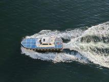 Blaues und weißes Boot pflügt die Oberfläche des blauen Meeres und hinterlässt eine Schaumspur Die Ansicht von der Oberseite stockfotografie