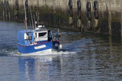 Blaues und weißes Küstenfischerboot laufend im Hafen von Lorient, Frankreich mit Lager im Hintergrund Lizenzfreies Stockfoto