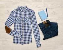 Blaues und weißes kariertes Hemd, Jeans, Handy, blaues Notizbuch mit Stift Hölzerner Hintergrund modernes Konzept Stockfotos