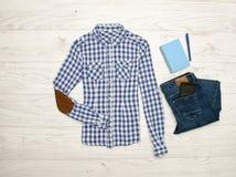Blaues und weißes kariertes Hemd, Jeans, Handy, blaues Notizbuch mit Stift Hölzerner Hintergrund modernes Konzept Lizenzfreie Stockfotografie