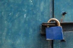 Blaues Vorhängeschloß auf Stahltür stockfotos