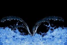 Blaues Wasser, das auf Schwarzem spritzt Lizenzfreie Stockbilder
