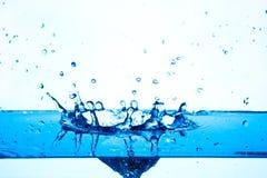 Blaues Wasser, das auf weißem Hintergrund spritzt. Stockfotos