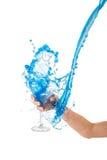Blaues Wasser, das im Glas spritzt Stockbilder
