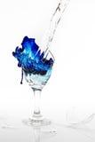 Blaues Wasser läuft ein defektes Weinglas auf weißem Hintergrund über Stockfoto
